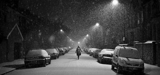 Одинокая фигура на заснеженной улице, снегопад, черно-белая фотография