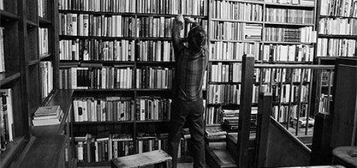 Черно-белая картинка, человек на фоне домашней библиотеки, книжные полки, много книг