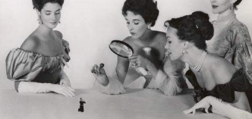 Женщины в платьях смотрят в лупу на лилипута, черно-белое фото